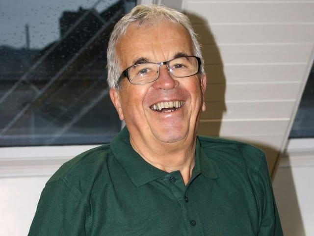 Markus Vogt mit grauen Haaren und Brille trägt ein dunkelgrünes Poloshirt und strahl in die Kamera.