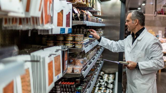 Ein Mann in weissem Arbeitskittel kontrolliert Produkte in einem Lebensmittelgeschäft.