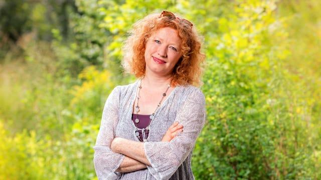 Ein Portrait einer Frau. Sie steht vor einer Blumenwiese.
