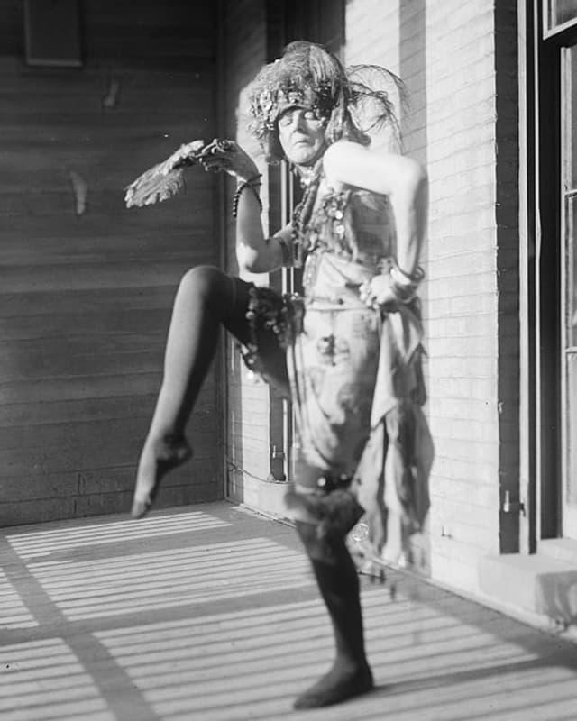 Eine Frau mit Federhut tanzt auf einem Bein.