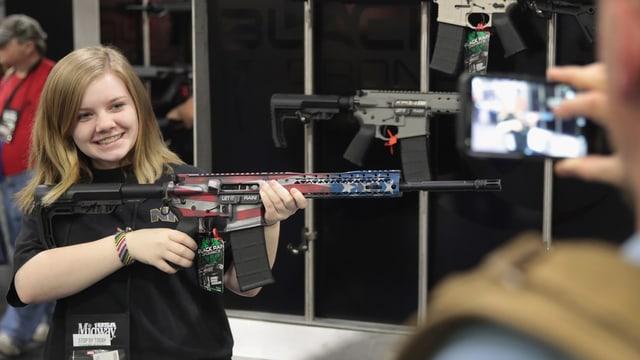 Ein Mädchen posiert mit einer Waffe.