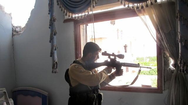 Ein Scharfschütze mit Gewehr an einem Fenster