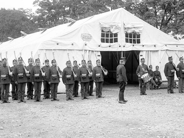 Schwarzweiss-Foto: Soldaten stehen vor einem grossen, weissen Zelt in Formation.
