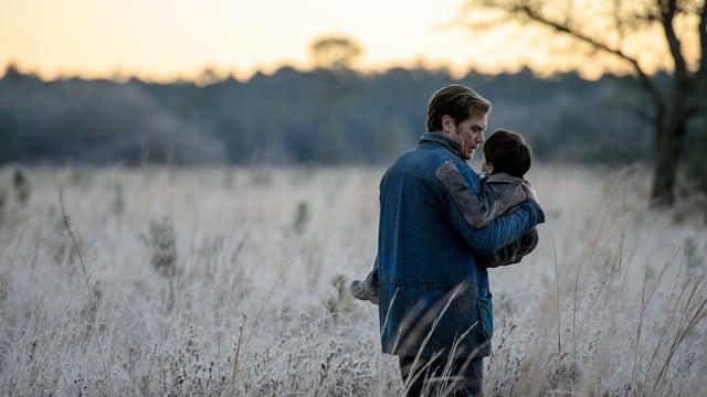 Ein Mann auf einem Feld, auf seinen Händen trägt er einen Jungen.