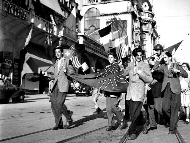 Eine Gruppe junge Leute zieht mit Flaggen durch die Strasse.