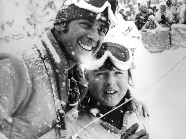 Schwarz-weiss Fotografie mit Adolf Ogi und Marie-Theres Nadig im Schneetreiben.