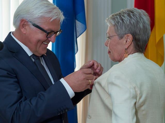 Deutschlands Aussenminister Steinmeier steckt Heidi Tagliavini das Bundesverdienstkreuz an.