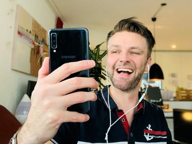 Mann in Wohnzimmer mit Handy in der Hand.