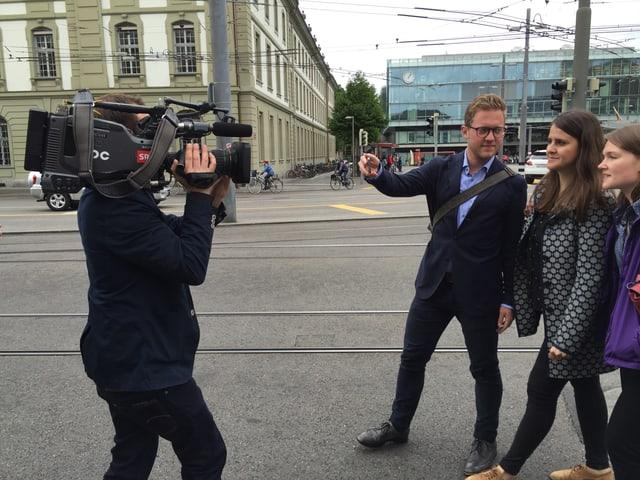 Kamermann filmt Student und ein Student filmen zwei Frauen und sich selber mit dem Handy.
