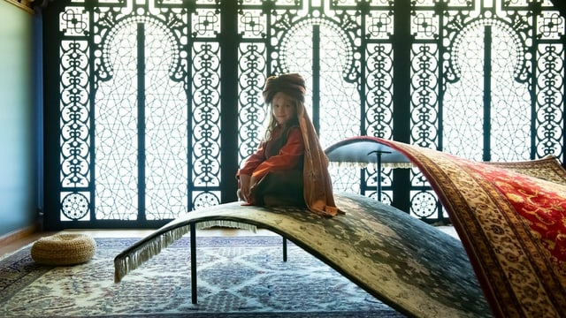 In einem orientalischen Palast hörend die Kinder Geschichten aus 1001 Nacht