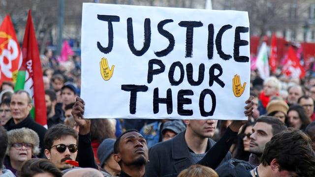 Demonstrant hebt Plakat hoch.
