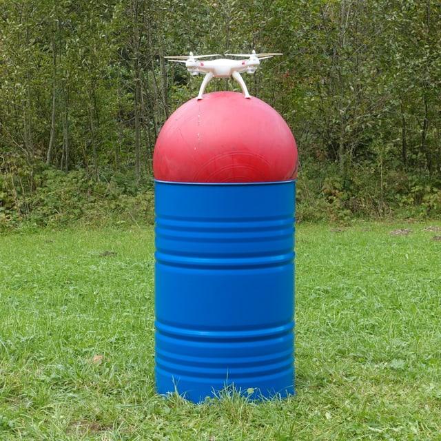 Eine Drohne auf einem Gymnastikball auf einem Fass auf einer Wiese.