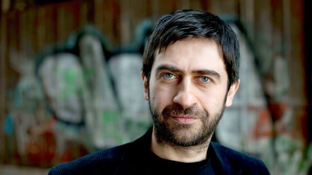 Emin Alper, Porträt nah, vor einer Wand mit Graffiti.