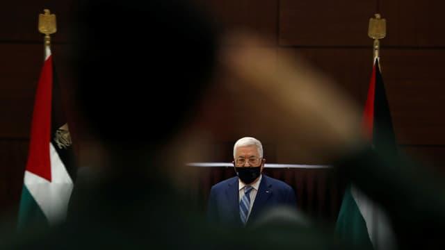 Mann mit Gesichtmaske zwischen zwei Palästinaflaggen.