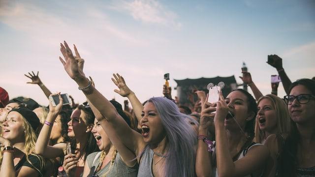Festivalaufnahme von jungen Frauen, die in Richtung Bühne schauen, mitsingen, die Hände in die Höhe halten oder Fotos machen.