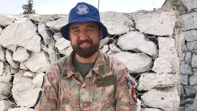 Mann in Kampfanzug mit Blauem Hut und Abzeichen.