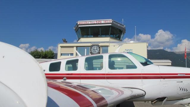 Flugzeug steht vor dem Flughafen-Hauptgebäude, wo auch der Tower dazu gehört.