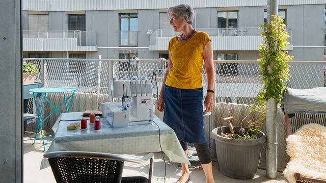 Eine ältere Frau auf dem Balkon mit Nähmaschine.