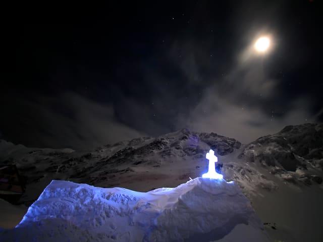 Der Mond scheint auf eine Kirche aus Eis in den schneebedeckten Bergen des Fagaras-Gebirges in Rumänien.