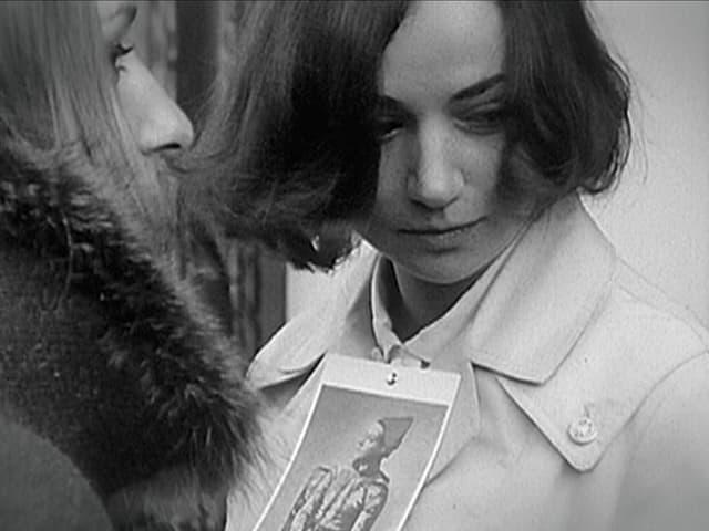 Junge Demonstratin trägt ein Foto am Blusenkragen von Picassos Harlekin.