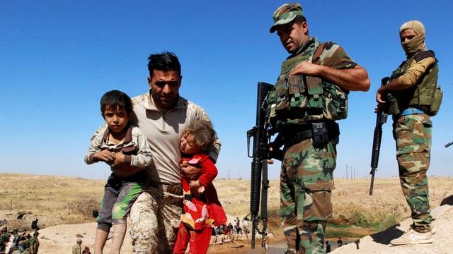 Irakische Soldaten beobachten einen Vater mit zwei Kindern unter den Armen bei der Flucht aus Hawidscha.