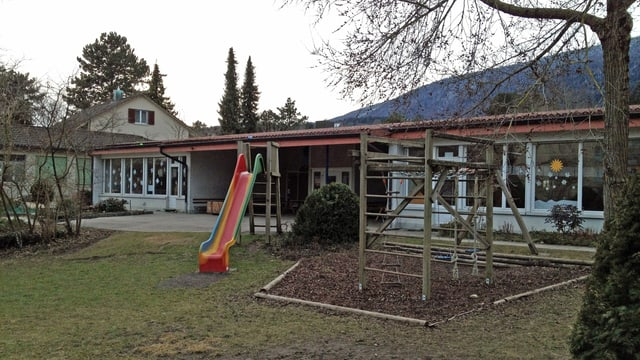 Ein älterer Kindergarten mit Spielplatz.