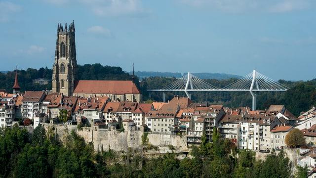 Der Stadtkern von Freiburg mit Kirche, dahinter die neue weisse Schrägseilbrücke