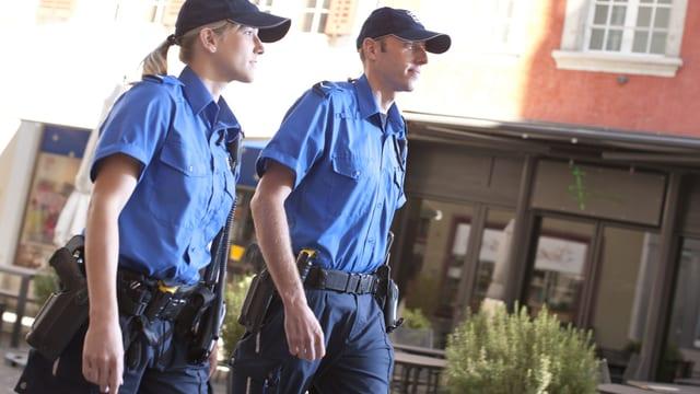 Eine Kantonspolizistin und ein Kantonspolizist patrouillieren zu Fuss.