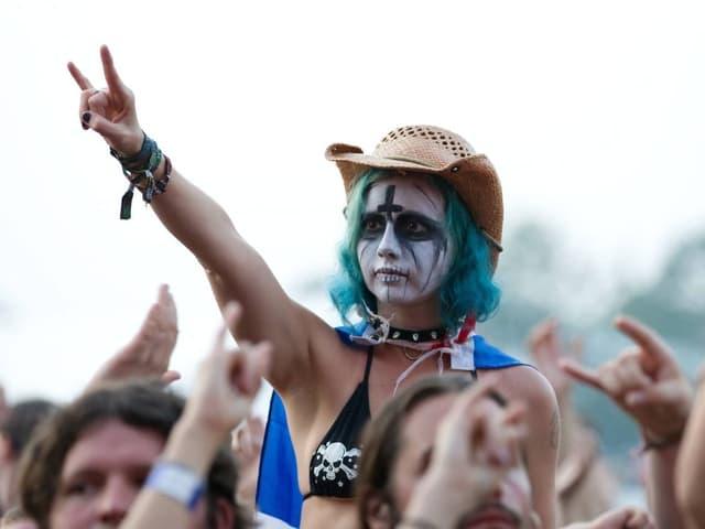 Eine Schwarz Weiss geschminkte Frau im Publikum eines Metal-Konzerts streckt die gehörnte Hand in die Luft.