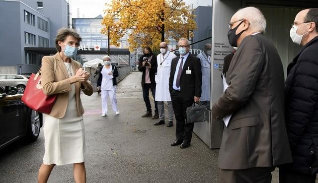 Simonetta Sommaruga geht mit Mundschutz vor dem Berner Inselspital auf Regierungspräsident Pierre Alain Schnegg zu.