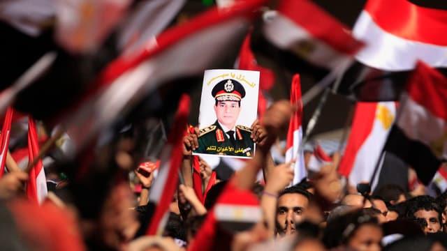 Befürworter von Abd al-Fatha al-Sisi halten sein Bild in die Höhe.
