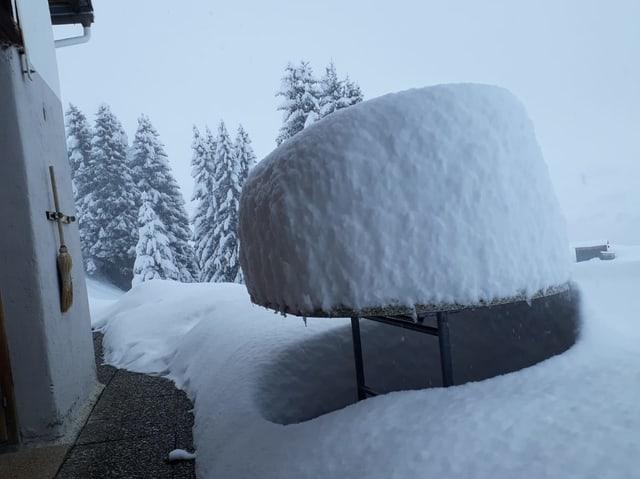 Auf einem Tisch liegt viel Neuschnee.