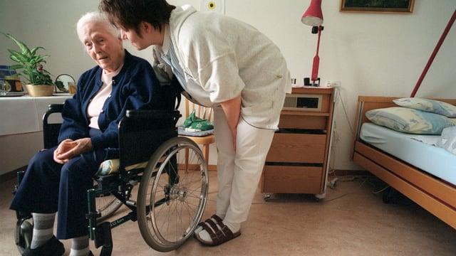Eine Pflegerin beugt sich vor zu einer älteren Dame die im Rollstuhl sitzt und etwas erzählt, die beiden befinden sich ein einem Zimmer im Altersheim.