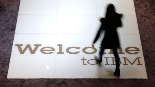 Die Silhouette einer Frau, die über ein IBM-Logo am Boden schreitet.