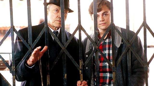 Zwei Männer stehen hinter einem Gitter