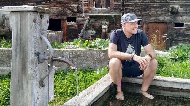 Reporter Marcel Hähni sitzt auf einem Brunnen.