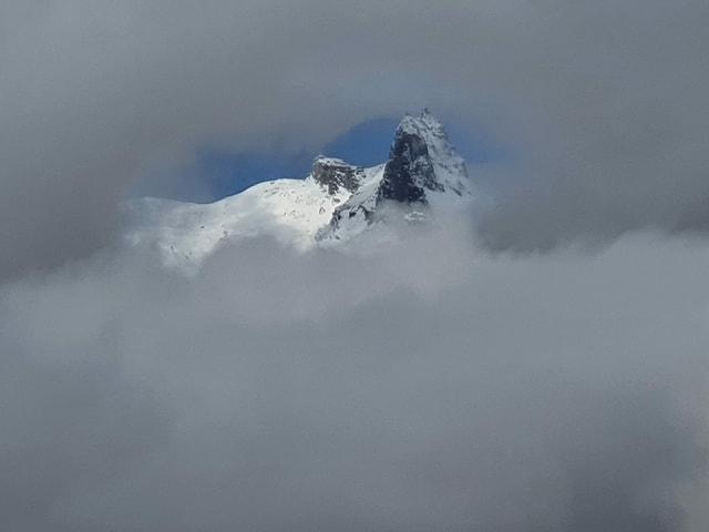Wolkenlücke mit einem Berg.