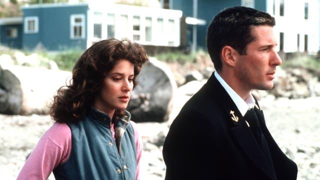 Debra Winger blickt traurig nach unten. Neben ihr Richard Gere der nachdenklich in die Ferne blickt.