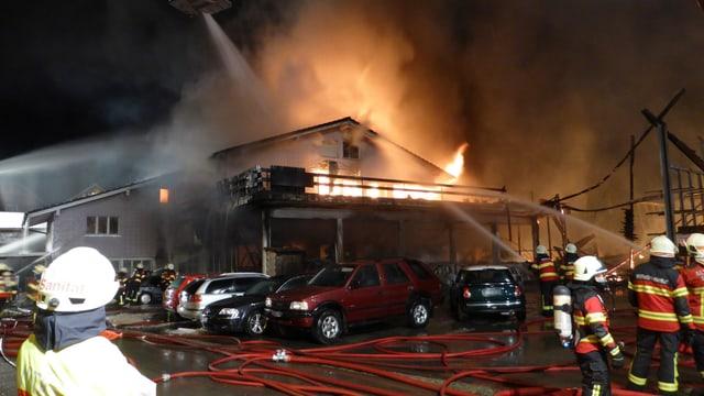 Brennendes Gebäude. Feuerwehrmänner löschen den Brand.