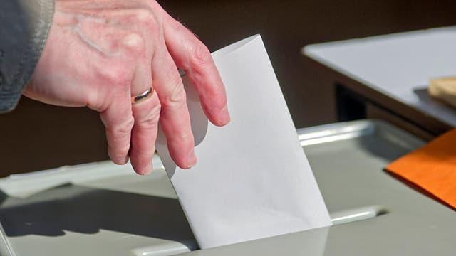 Ein Wähler wirft einen Wahlzettel in eine Urne.