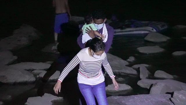 Mann mit Säugling und Frau klettern vom Schlauchboot über Steine ans Ufer.
