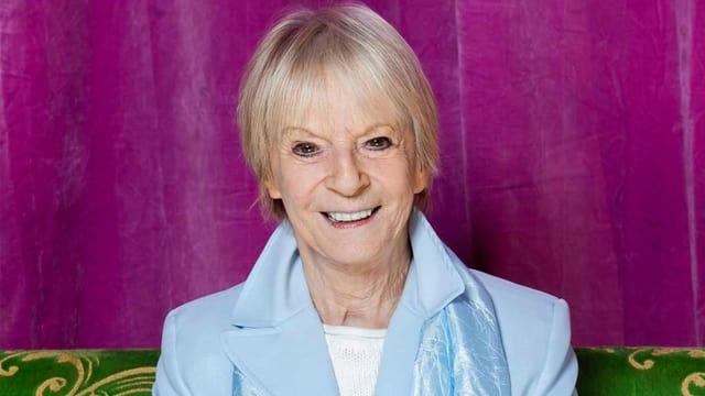 Eine lachende Frau mit kurzen blonden Haaren.
