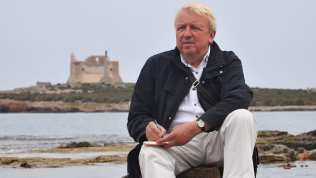 Ortheil sitzt mit einem Notitzbuch auf einem Stein am Meer.