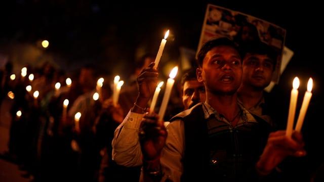 Männer halten in gedenken an eine Studentin Kerzen.
