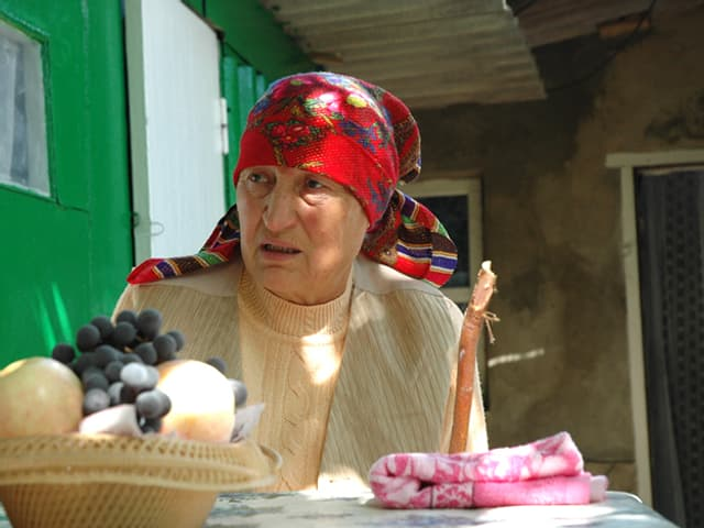 Eine alte Frau mit Kopftuch sitzt an einem Tisch.