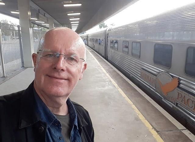 Urs Wälterlin macht vor dem langen, silbernen Zug mit der Aufschrift «Indian Pacific» ein Selfie. Im Hintergrund sieht man den Bahnsteig.