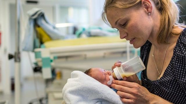 Frau gibt einem Baby die Schoppenflasche