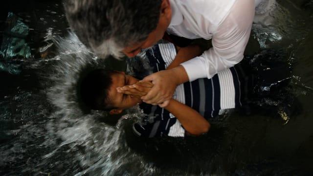 Ein Mann taucht ein Kind ins Wasser. Es handelt sich um eine Taufe.