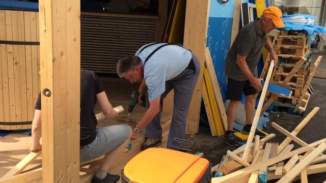 Männer arbeiten mit Holz.