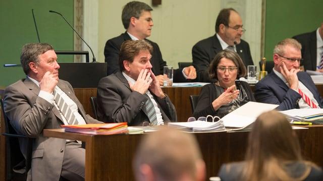 5 Männer und eine Frau sitzen in Bänken im Kantonsrat Zug.